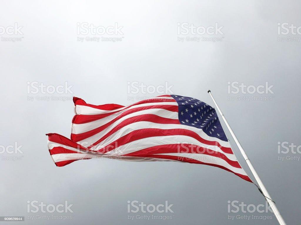 Amerikanische Flagge auf dem Hintergrund der düsteren Himmel. Flagge der Vereinigten Staaten fliegenden Halbmast. – Foto