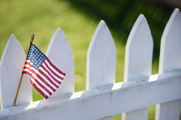 American Flag on White Picket Fence stock photo