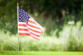 American flag outdoors in a yard in front of a field.