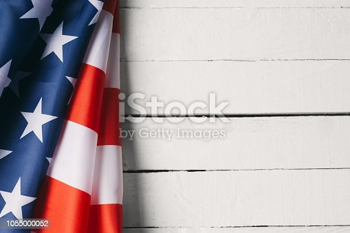 971061452 istock photo American Flag Over Wood Background 1055000052