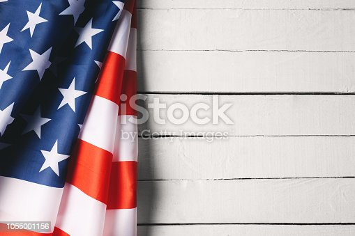 971061452 istock photo American Flag Over Wood Background 1055001156