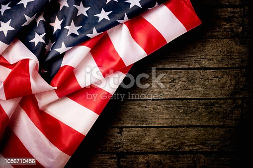 971061452 istock photo American Flag Over Wood Background 1056710456