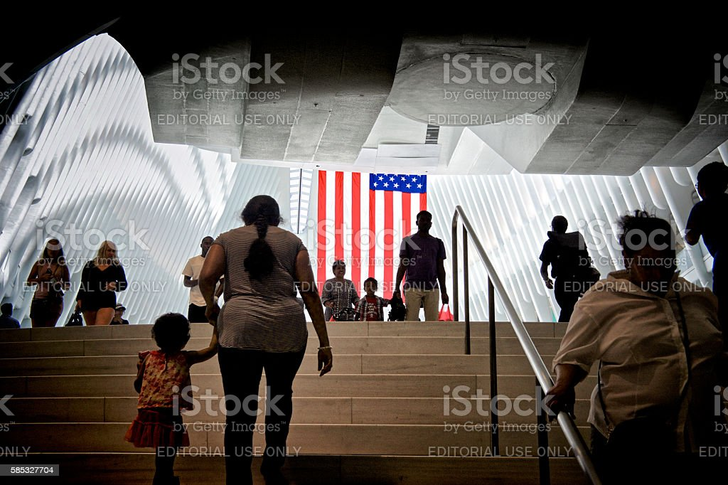 American Flag, People Passing Through World Trade Transportation Hub, NYC New York City, USA - July 02, 2016: People passing beneath a large American flag inside the World Trade Center Transportation Hub at Ground Zero, World Trade Center site, Lower Manhattan. 21st Century Style Stock Photo