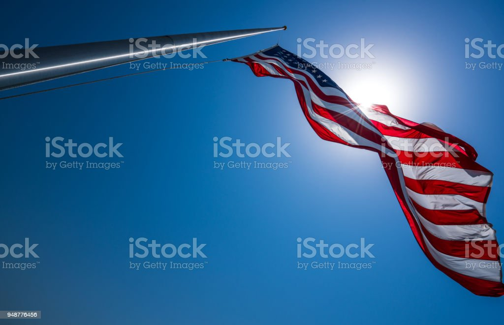 American Flag perfect flagpole and looking into sun stock photo