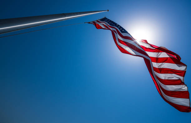 American Flag perfect flagpole and looking into sun American Flag perfect flagpole and looking into sun with perfect blue sky flagpole stock pictures, royalty-free photos & images