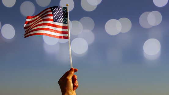 Hand holding American flag against  blue sky with sunny bokeh, vintage toned image