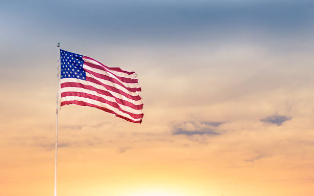 American flag American flag blowing in the wind against beautiful sunset. independence day photos stock pictures, royalty-free photos & images
