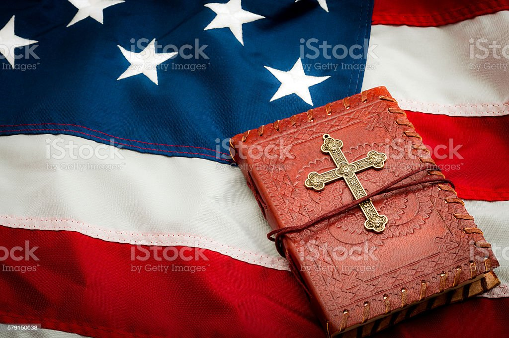 American flag, red vintage bible with a gold cross stock photo