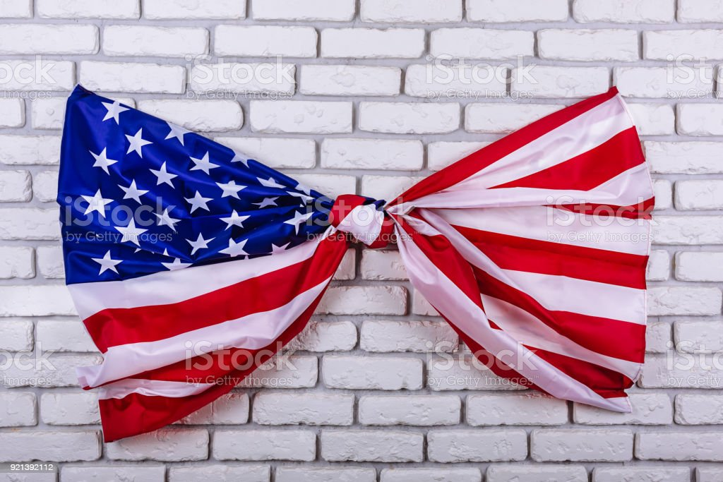 American flag, tied in a knot, on a white brick wall. Visual concept of preparation for Independence Day. Fourth of July patriotic consept stock photo