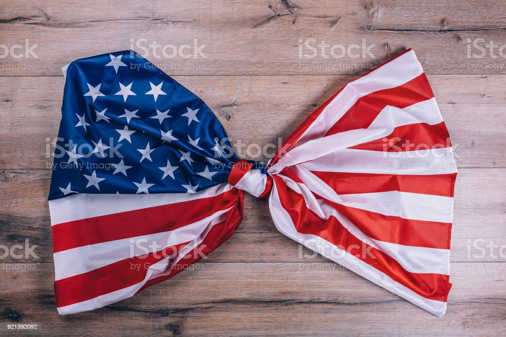 American flag, tied in a knot, on dark wooden wall. Visual concept of preparation for Independence Day. Fourth of July patriotic consept stock photo