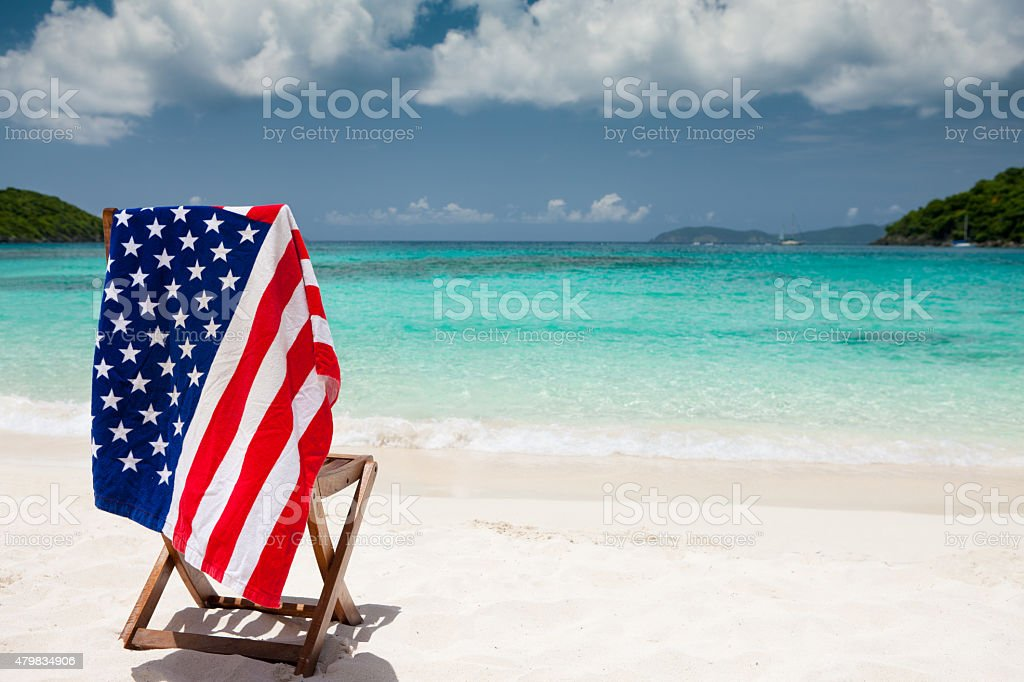 American flag towel over beach chair in US Virgin Islands stock photo