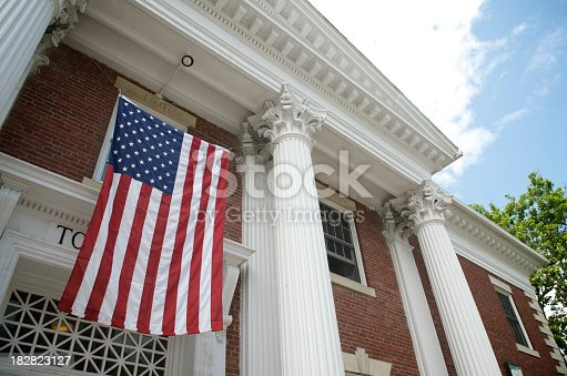 American flag hangs between the white columns of a traditional colonial style town hall building