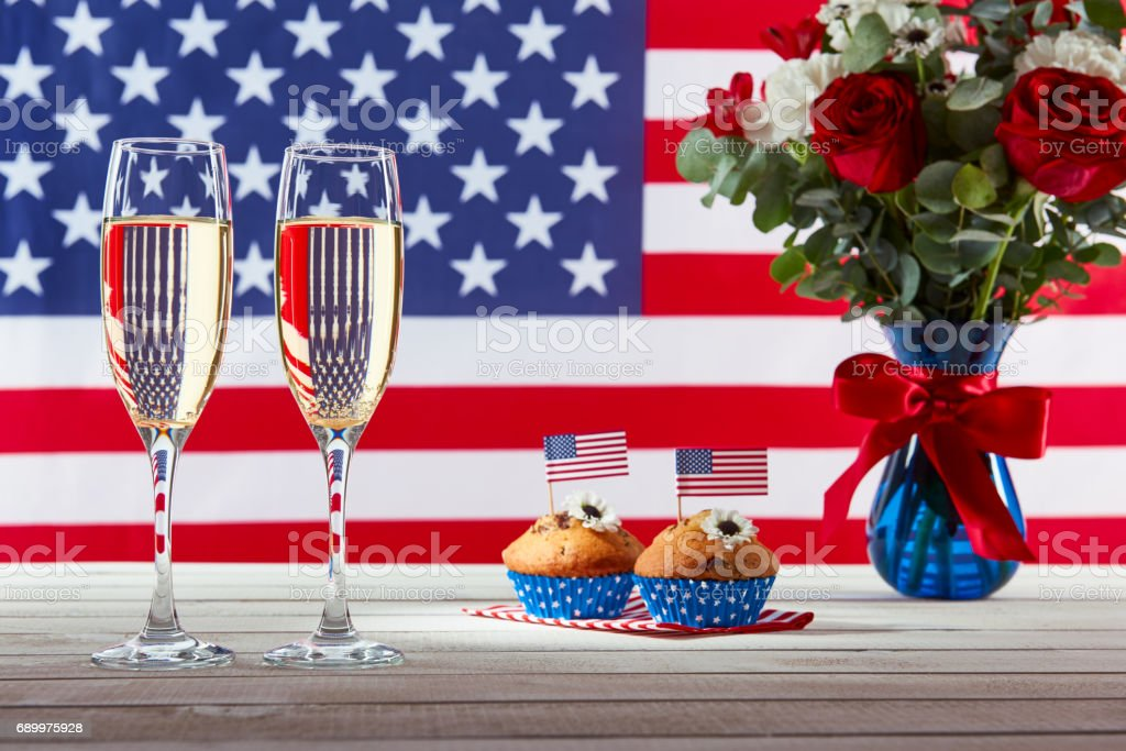 American flag, two glasses of champagne and cute cupcakes stock photo