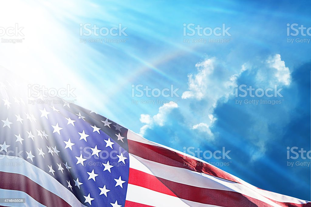 American Flag Under Blue Sky With Rainbow stock photo