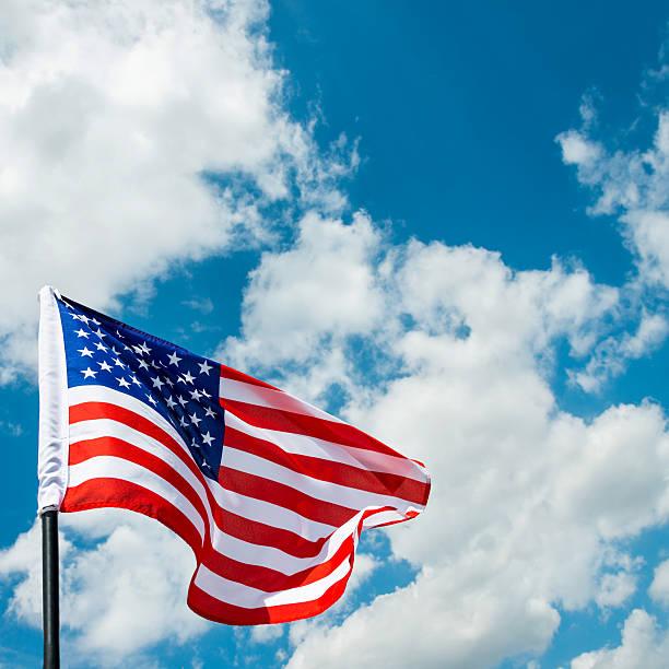 American flag waving against blue sky stock photo