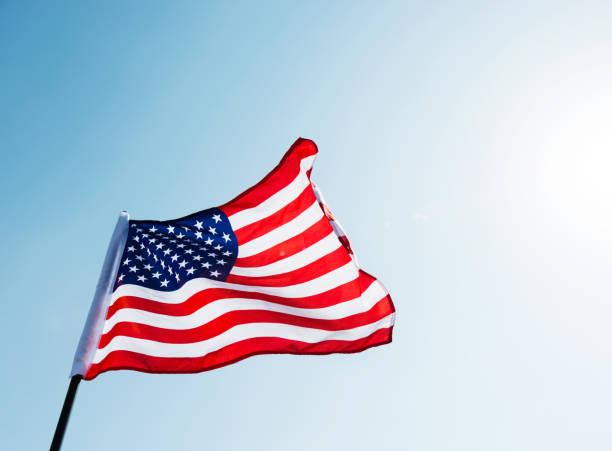 amerikanische flagge winken gegen blauen himmel - pfosten stock-fotos und bilder