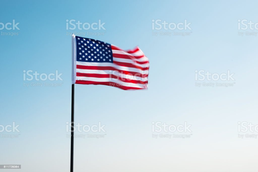 American flag waving against blue sky stock photo
