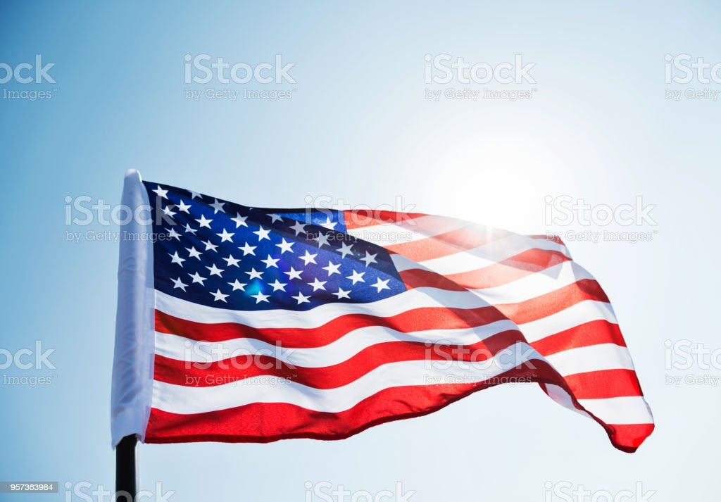 American Flag Waving Against Blue Sky Stock Photo - Download