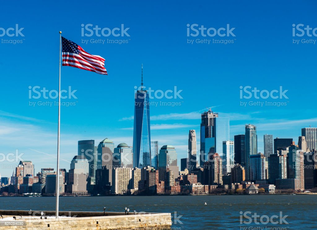 American flag waving against One World Trade Center in Financial District, Lower Manhattan, New York City stock photo