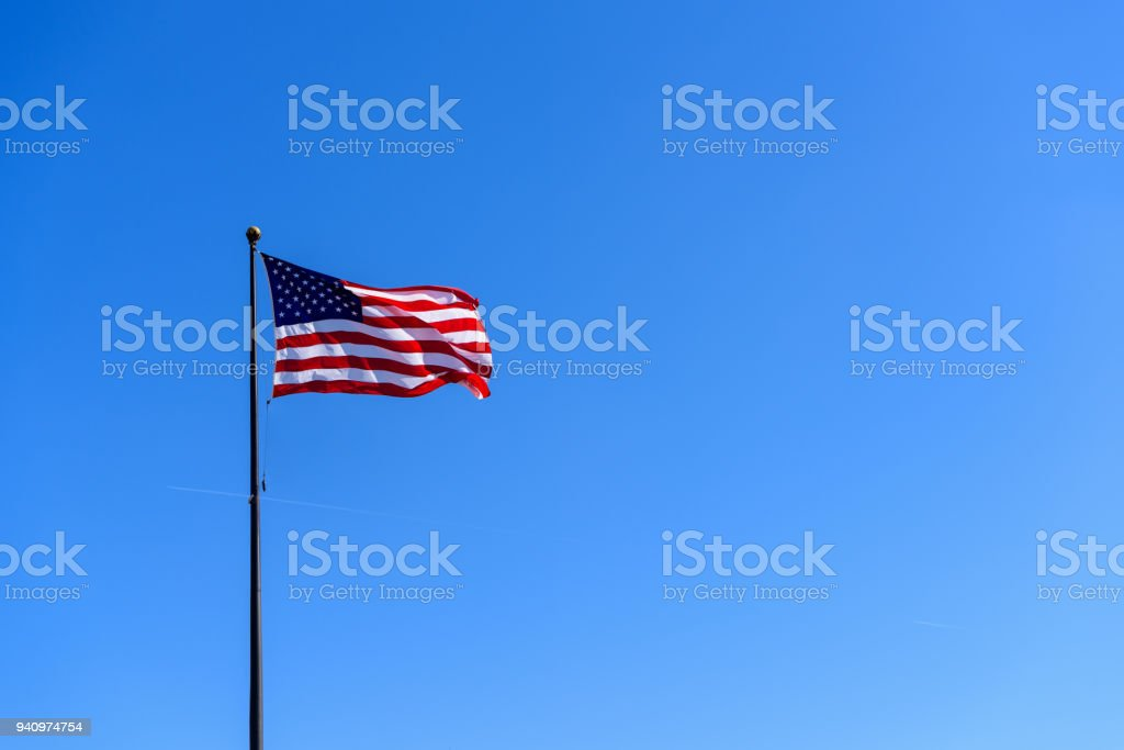 American flag waving against solid blue sky stock photo