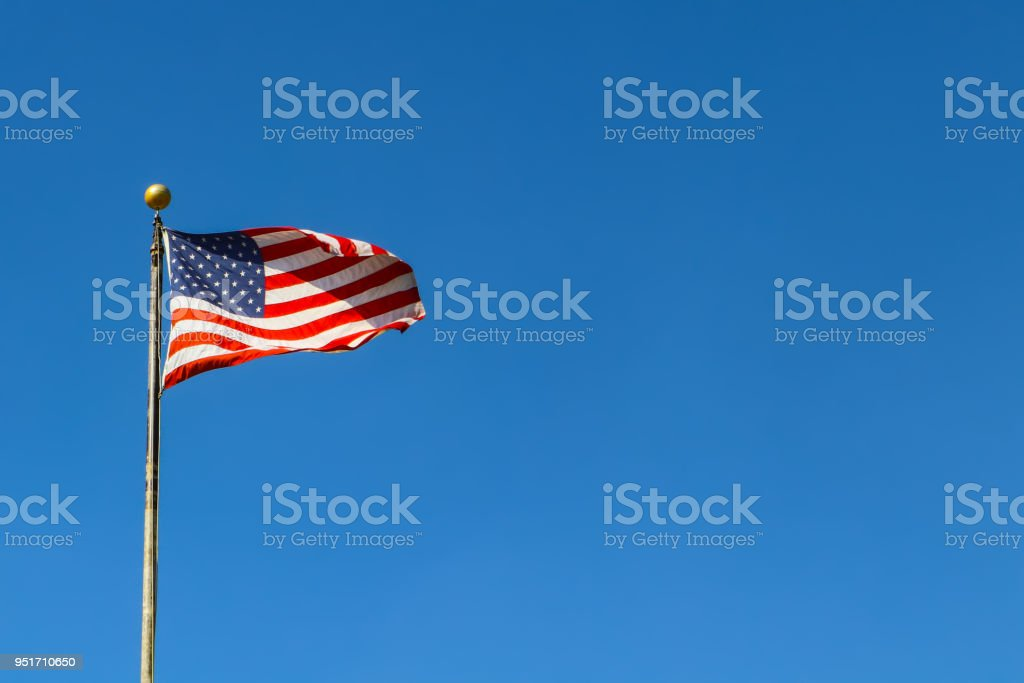 American Flag waving against very blue sky on flagpole - room for copy stock photo