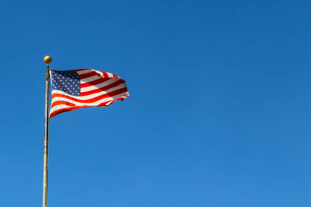 american flag waving against very blue sky on flagpole - room for copy - national anthem stock photos and pictures