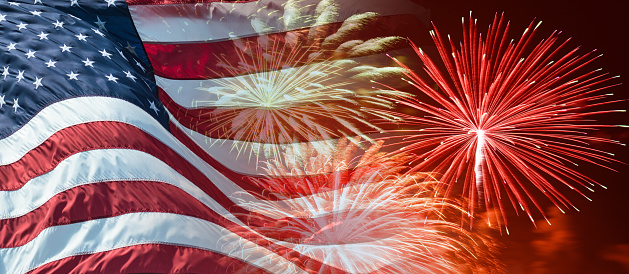American Flag Waving For A National Holiday With Fireworks Stock Photo - Download Image Now