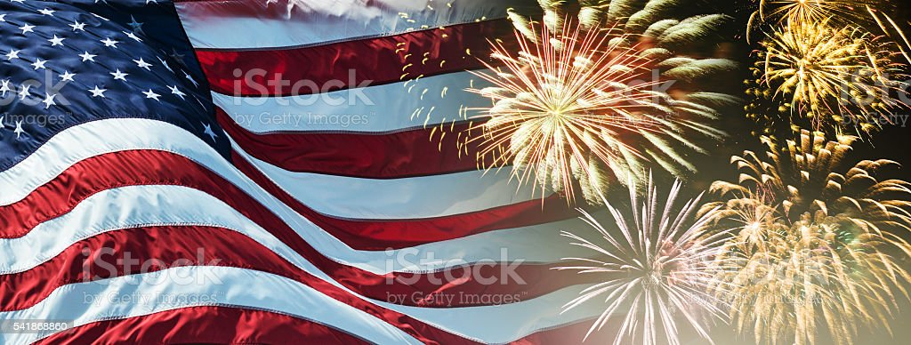 american flag waving for a national holiday with fireworks royalty free stock photo