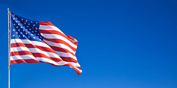 american flag waving in blue sky - american flag stock pictures, royalty-free photos & images