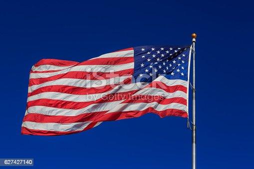 istock American flag waving in blue sky 627427140