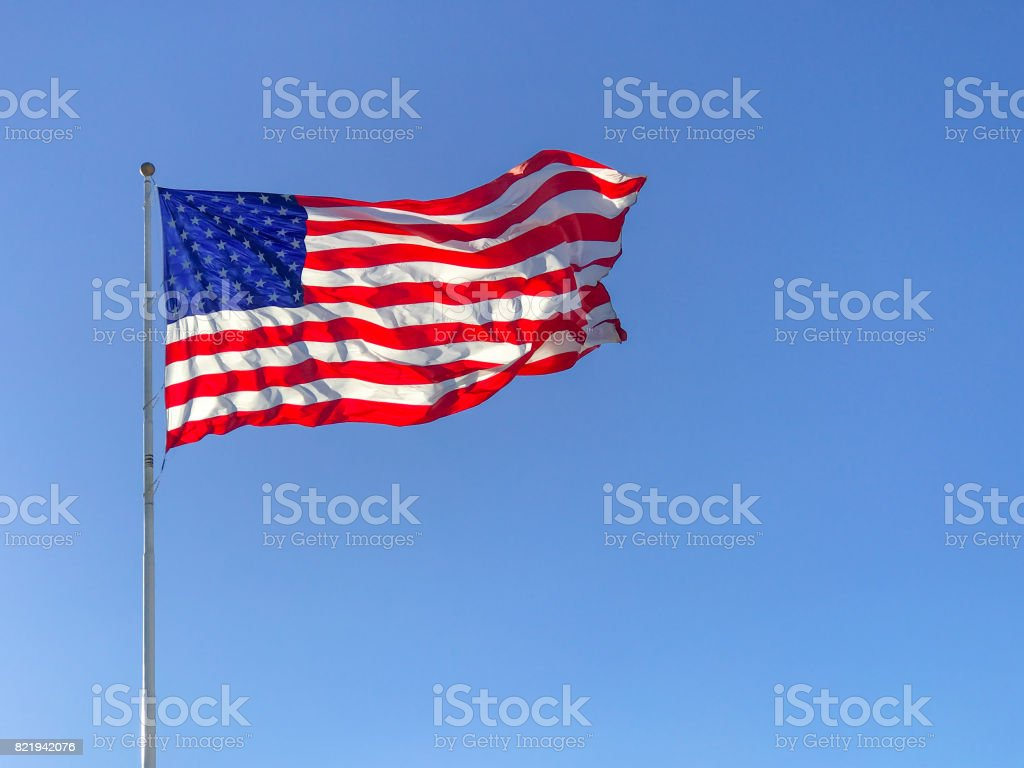 American flag waving in blue sky. stock photo