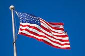 istock American flag waving in breeze on pole 157605738