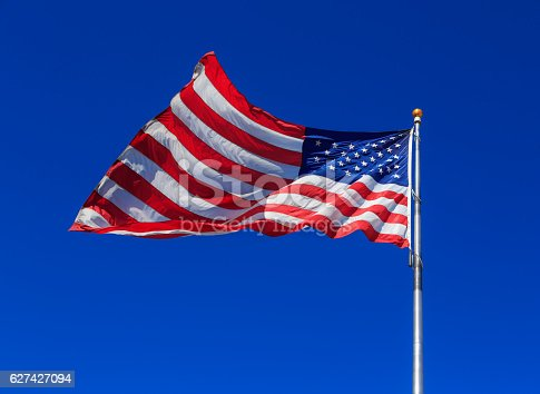 947881968istockphoto American flag waving in clear blue sky 627427094
