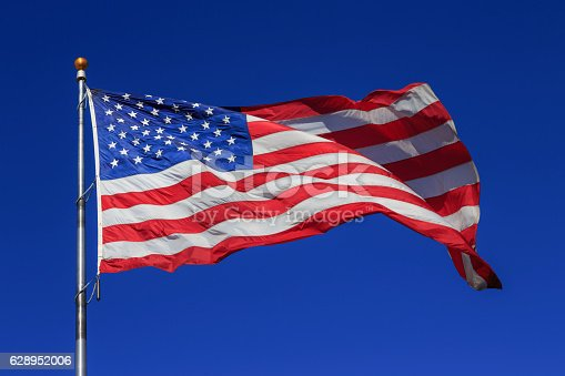 istock American flag waving in clear blue sky 628952006