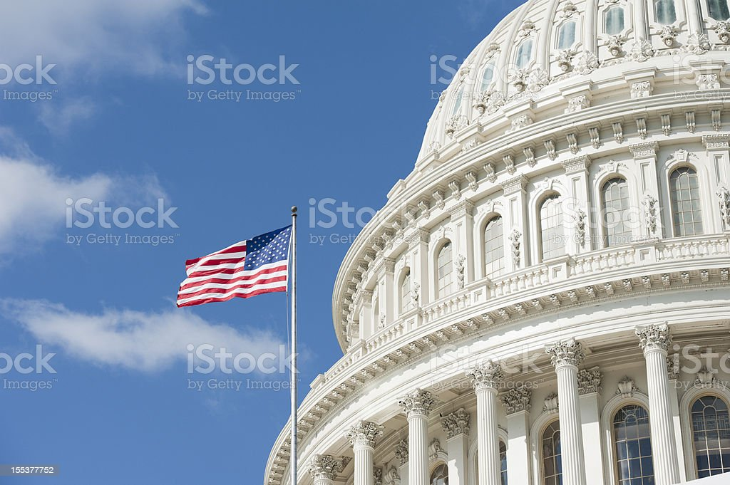 American flag waving in front of Capitol Hill stock photo