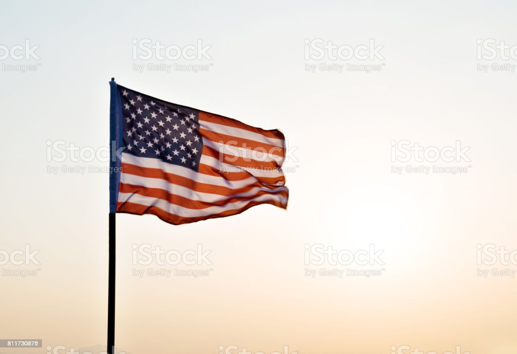 American flag waving in sunset stock photo