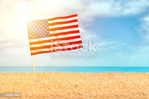 483422527istockphoto American flag waving in the sand on the beach 1195561824