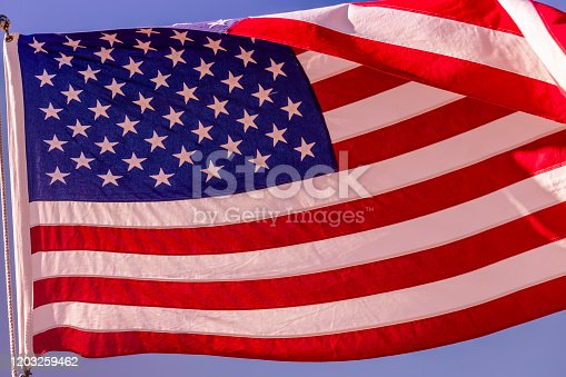 937074172 istock photo American flag waving in the sky – United States of America, North America 1203259462