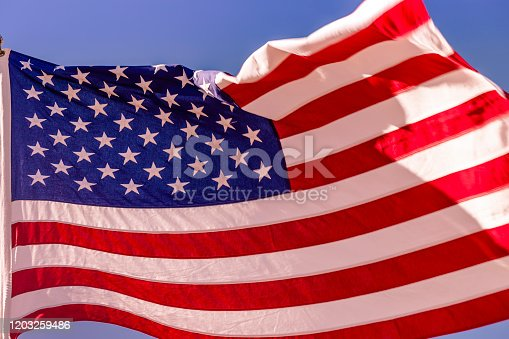 937074172 istock photo American flag waving in the sky – United States of America, North America 1203259486