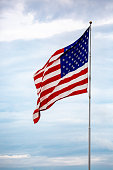 istock American flag waving on a flagpole in front of clouds 1183250506