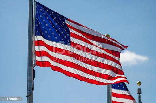 840615050 istock photo American flag waving on pole 1217896641