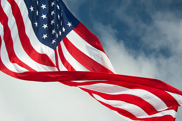 American flag waving with sky and big clouds behind stock photo