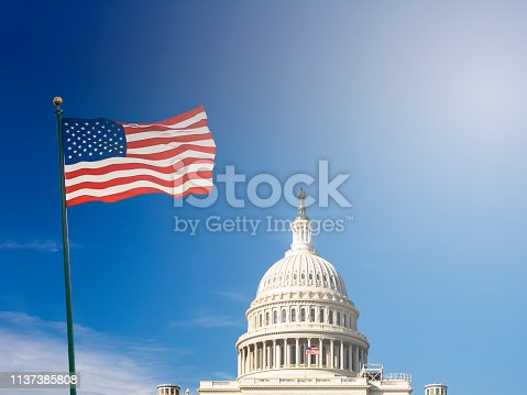 American flag waving with the Capitol Hill in the background