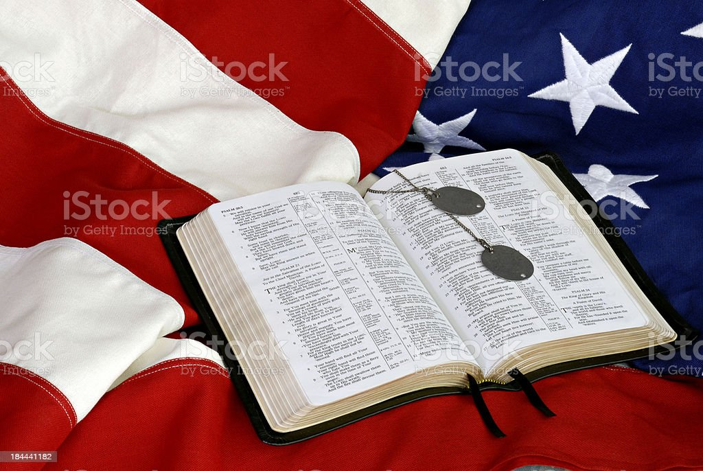 Open Bible on American flag with WWII dog tags.