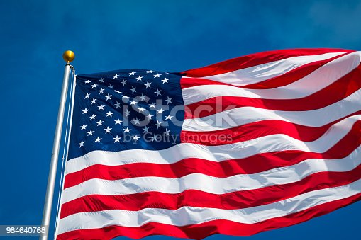 537898300istockphoto American Flag with perfect blue sky background looking up at Flagpole 984640768
