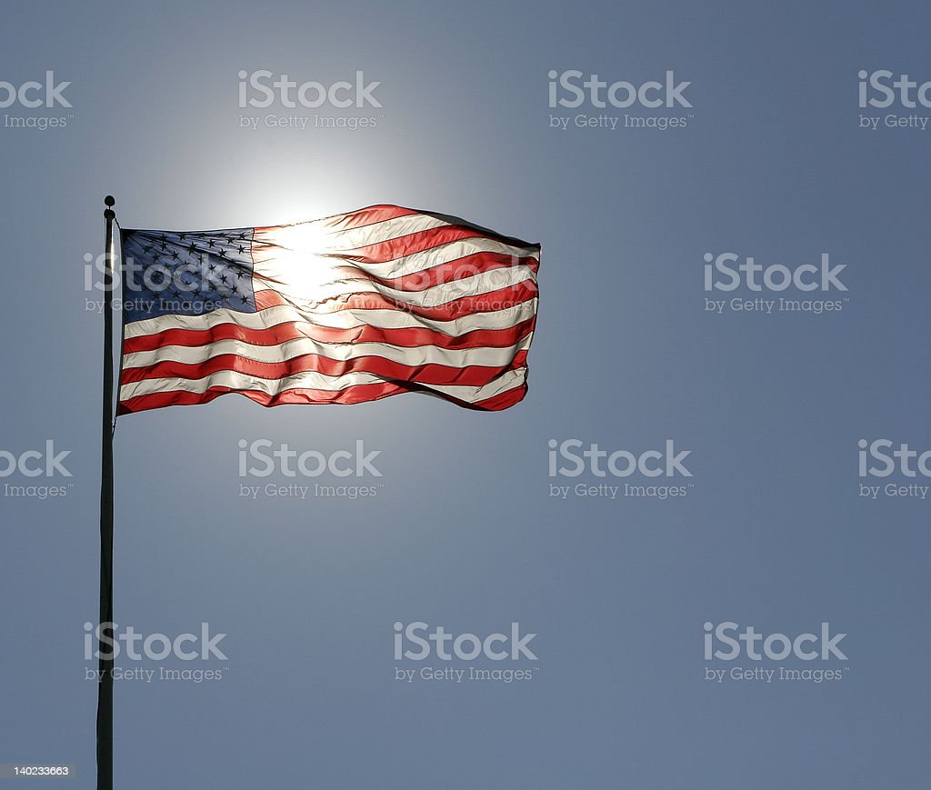 american flag with sun behind stock photo
