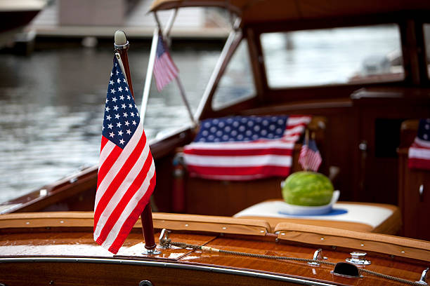American flags adorn a classic wooden boat at anchor stock photo