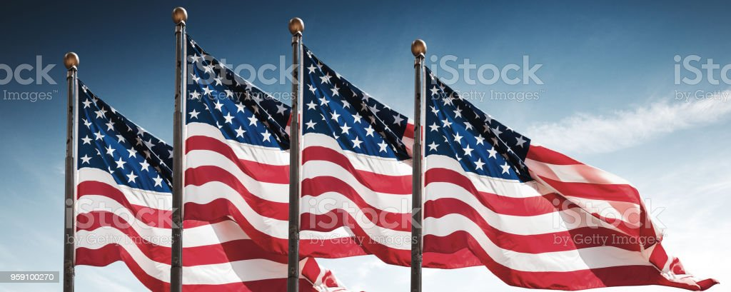 american flags against the sky stock photo