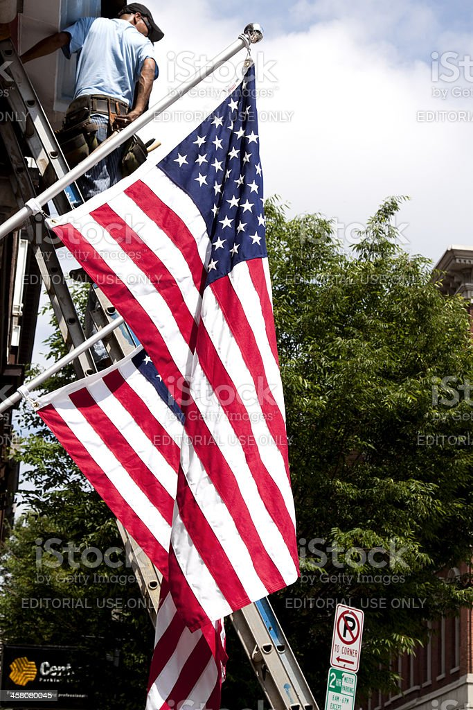 American Flags and Men on Ladders stock photo