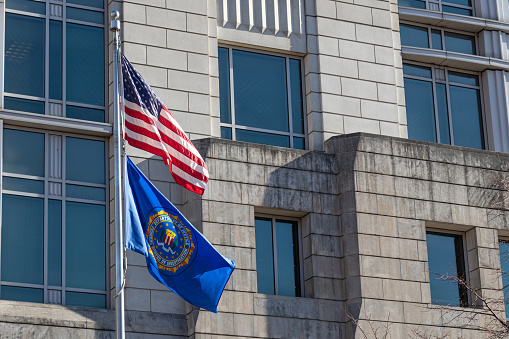 Seal of the FBI on a flag and American flag waving at their field office in D.C.